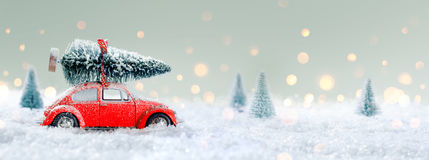 red-car-carrying-christmas-tree-snowy-forest-77615139